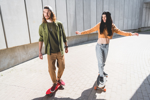 couple riding penny skateboards